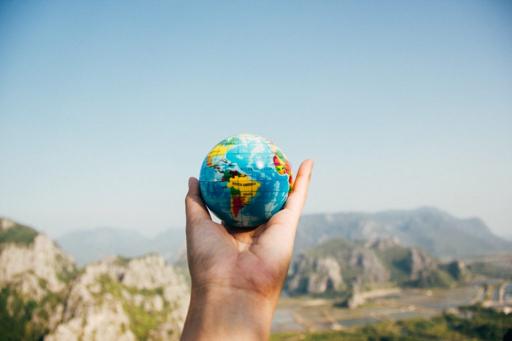 Eine Hand hält eine Weltkugel - Wie sieht dein Weltbild aus?