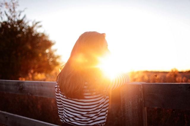 Weiterentwicklung - Fröhliche Frau auf einem Balkon vor dem Sonnenuntergang