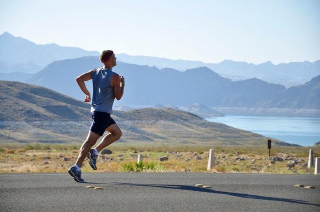 Motivation zum Sport: Eine Person joggt auf einer Straße mit Bergen im Hintergrund