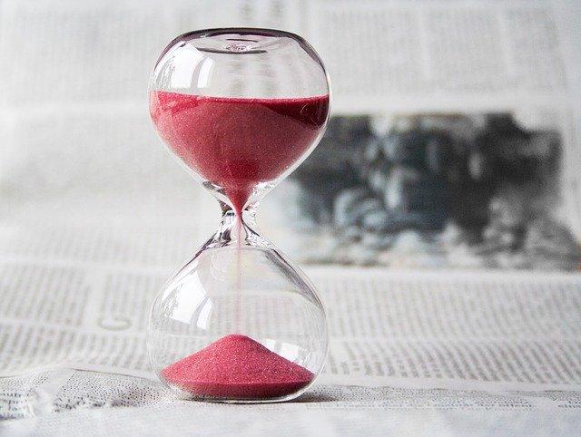 Selbstmotivation lernen - Sanduhr mit rotem Sand auf einer Zeitung